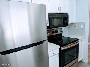 Lovely quartz and stainless appliances with white cabintes!