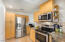 Kitchen with pantry, stainless steel refrigerator, built in microwave and stove, oven combo.