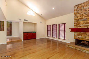 Great room with 19 foot ceiling, stacked stone wood-burning fireplace, wet bar, surround sound speakers, bamboo flooring