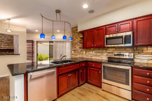 Cherry stained cabintry, SS appliances, granite, stacked stone accents, pendant lighting.