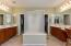 Walk in center shower separates dual sinks with separate garden tub tucked in the corner, private toilet room, large walk in closet.