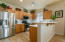 Kitchen with Stainless Appliances, Smooth Cooktop Range, Raised Panel Cabinets and Corian Counters