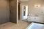 Master bathroom: his vanity area. Door leads to patio. Zero grade shower with multiple shower heads.