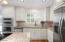kitchen features white cabinetry, stainless appliances & light colored granite