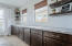 Built in buffet cabinets in dining room with granite countertops and floating wall shelves.