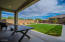 Extended covered patio looking out to your real grass yard, raised garden beds and four varieties of fruit trees