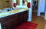 Dual undermount sinks and granite counters with plenty of space, plank tile flooring