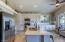 Granite slab countertops, crisp white cabinets, and modern oil-rubbed bronze hardware.