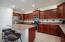 Kitchen island, pantry, granite countertops, and gas stove