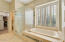Separate tub with shuttered windows above and generous shower.
