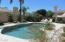 Beautiful desert landscaping creates an inviting backdrop for this Pebble Tech pool w/self cleaning feature