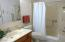 Bathroom features cut down tub feature, large mirrored medicine cabinet, emergency pull cord, grab bars, linen closet and heat lamp