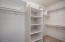 This walk-in closet is spacious and connected to the master bath.