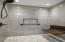 Floor to ceiling tile with folding bench, glass door and linear drain.