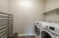 Ample space for additional laundry room cabinets. Front load washer/dryer convey.