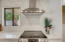 Gleaming stainless steel range and range hood complements the custom glass tile backsplash