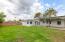 large grassy yard with pergola.