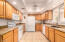 Kitchen with granite counters, raised panel cabinets and smooth top stove.