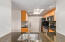 Modern Kitchen with Granite Countertops, Stainless Steel Appliances, Blonde Cabinets with Opaque Glass Features, Classic Backsplash and Eat Up Bar