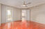 Owners Suite featuring Cherrywood Manufactured Floors, Modern Ceiling Fan & Light, Glass Door to Balcony overlooking 16th Green of Stone Creek Golf Course, with ensuite Bathroom & Large Closet