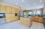 Panoramic view of the left side of the kitchen and its maple cabinets