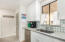 Tall, modern, white kitchen cabinets play nicely with the quartz countertop