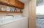 Laundry closet easily fits full size washer/dryer plus storage cabinetry & shelf