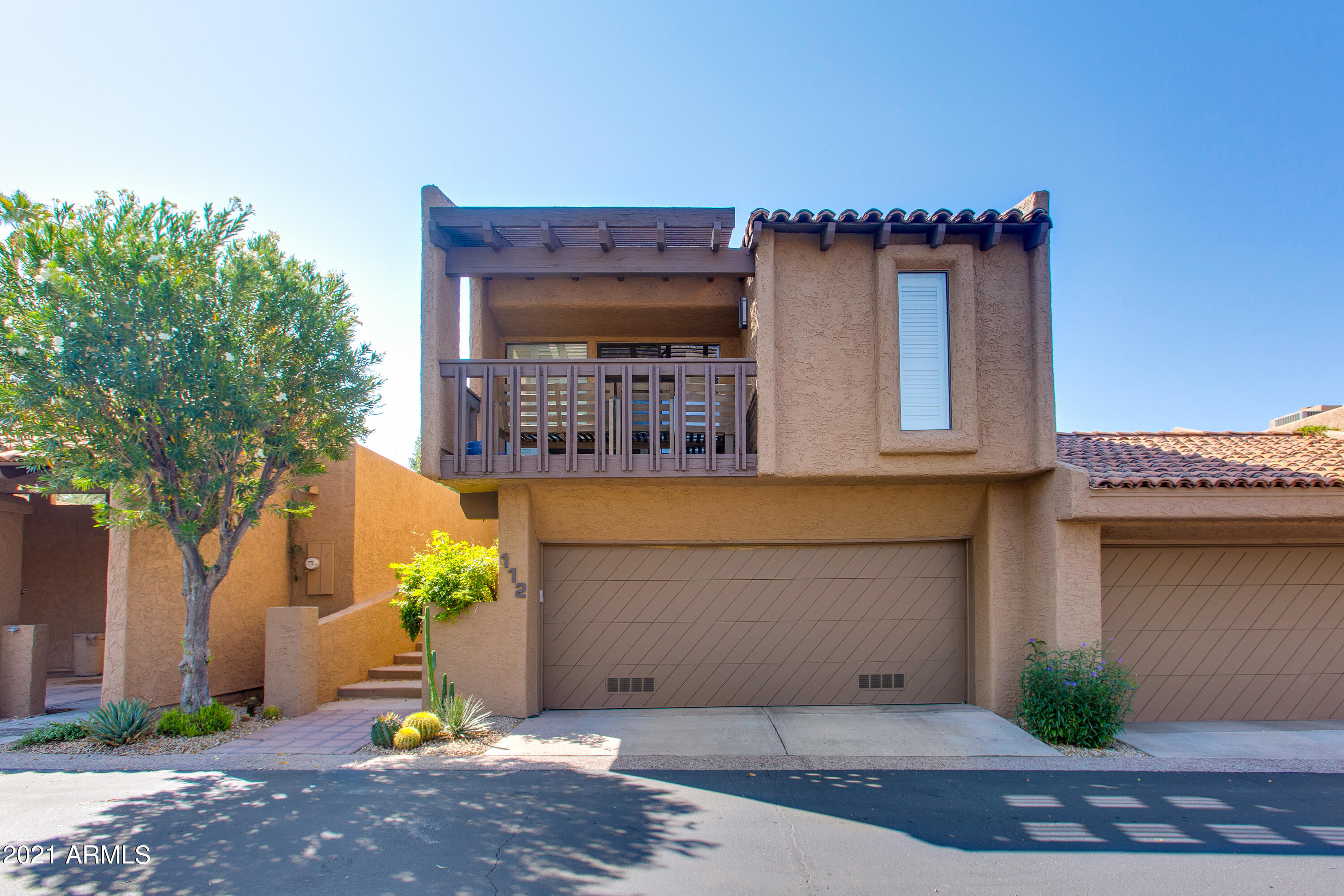 Tastefully designed and elegantly updated, this townhome features 3 bedrooms and 2 and a half baths and will impress the most discerning of buyers. Nestled within the 24-hour guard gated community of The Village at Camelback Mtn. this townhome is well appointed throughout and is completely turnkey. As you enter, a towering fireplace with custom stonework lies as the centerpiece of the great room, which also features a soaring vaulted ceiling. Pristine Brazilian Cherry hardwood floors adorn the first floor living spaces. A custom wet bar with built-in wine fridge and wine room make for the perfect entertaining spot. The kitchen boasts new white granite countertops and overlooks the professionally landscaped patio. The master suite features a separate sitting room, walk-in closet and private balcony, which affords stunning views of Camelback Mtn. The spacious master bath is equipped with a generously sized shower with custom tile work and a soaking tub. 2-car garage, ample storage, plantation shutters, Lutron lighting system and more. Unbeatable location: walking distance to numerous Arcadia restaurants, AJ's Fine foods, Steak 44, The Village Health Club and the new Global Ambassador Hotel which is coming soon.