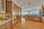 Fully equipped kitchen with stainless steel counters and open to a walk-in pantry