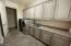 Laundry room with kitchen quality cabinetry and storage.