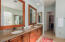 The owner's bathroom is upgraded with a double vanity, granite countertops, wood framed mirrors, and a built-in hamper.