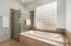 Updated shower and jacuzzi bath are surrounded by tile and stone. Glass block and seeded glass at the shower offer privacy.