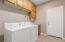 The laundry room has a sink and ample cabinetry.