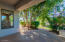 """The """"small"""" patio is shaded by a luscious ficus tree and green shrubbery."""