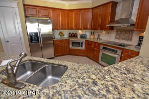 Stainless steel appliances including a ventilation hood. Stone surface counters, tile backsplash with ornate accents.