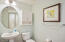 The guest bath features a lovely pedestal sink and walk-in shower.