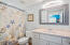 The master bath has been updated with a Quartz vanity and contemporary lighting and features a shower/tub combo.