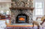 LIVING ROOM STONE FIREPLACE HAS A WOODSTOVE INSERT THAT WARMS THE ROOM