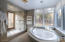 soaking tub, walk in shower with glass window open to natural light