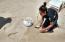 Sea Turtle Release Program biologist Staff Member gathering the eggs to take them to incubation pen