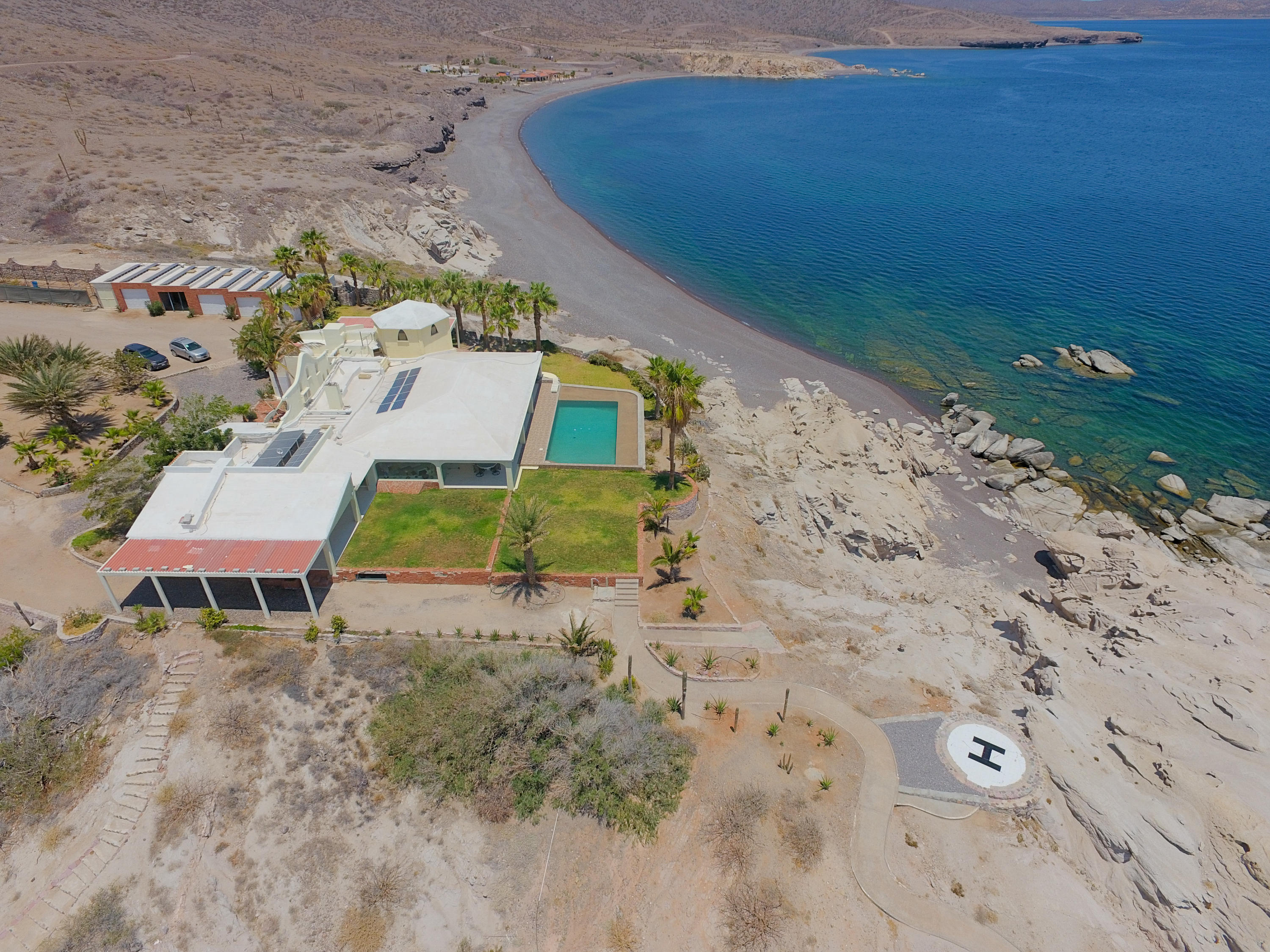 Luxurious, off-grid living in the remote beauty of the Sea of Cortez.This unique 114.6 acre estate sits on a bluff perched over a secluded, picture perfect cove surrounded by white sand beaches along the Sea of Cortez.  This gem has a dominating view of the islands of Cerralvo and Espiritu Santo. With over three hundred days a year of sun, you will be greeted almost daily by dolphins, manta rays whales and fish.  This is an ideal property for nature lovers and outdoors enthusiasts alike to enjoy hiking, swimming, snorkeling, fishing, paddle boarding, kite surfing and a myriad of other options.This luxurious property is completely self sufficient.  Water is provided by a solar operated desalination plant which was created by the seller. He also designed 2 water treatment plants.  Together, they deliver over 4,000 gallons of water a day, enough to irrigate the 200 trees and plants as well as the 2 acres of lawn and the 3 vegetable gardens.  The property also has energy collection capabilities by way of 50 KW (p) PV panels, stored in 432 L16 batteries.    The Cove at La Paz has multiple structures on site.  A lovely 7,000 square foot 3 bedroom home with a stunning fresh water swimming pool, 2 large garages, a fully equipped carpenter and machine workshop, a boat garage (with a 24ft. Catamaran power boat - two 115 HP Yamaha outboard motors) and 2 live-in caretaker homes. All sit on a bluff above a completely secluded 300 meter sandy beach cove where you will find two lovely guest houses.