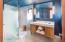 he bathroom in the second bedroom features a dual head rain shower.
