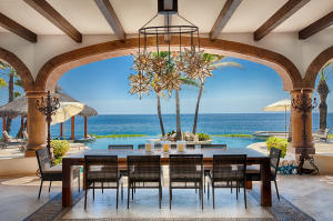 Exposed wood beams, archways and picturesque views. Photo of covered exterior dining area