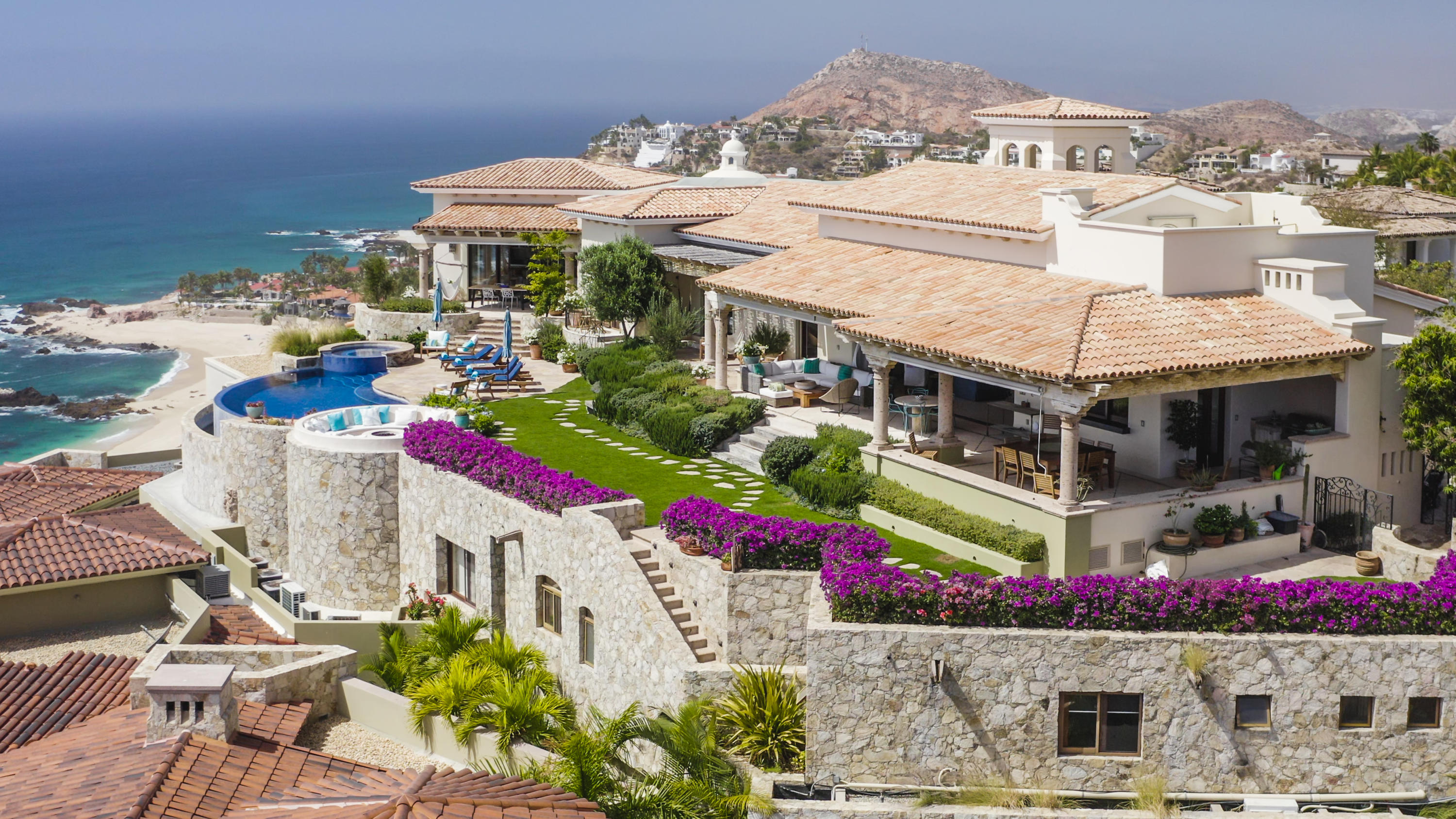 A hilltop sanctuary sitting at an altitude of 300 ft above the ocean, giving a unique and relaxed wide open setting that will keep your mind at ease. Exceeding 200 degrees of extensive panoramic views, overlooking above and beyond the Sea of Cortez, golden beaches and city lights of San Jose del Cabo. At the heart of the luxury, gated community of La Montana in Villas del Mar. This laid-back beach house has the perfect balance between traditional Mexican hacienda style and contemporary architecture. Villa Corazon was thoughtfully designed to block the least amount of views, uniting the inside to the outside through pocket doors and high ceilings to make the most out of year round great weather, giving priority to the flow of cool air and the enjoyment of views from inside. Main House: 5 bedrooms with en suite bathrooms TV room / Library Underground wine cave and bar  Maid quarters with kitchenette  Two fully stocked kitchens  Multiple living spaces Infinity pool with large deck and garden 2 car indoor garage and 1 carport    Casita: 2 Bedrooms with en suite bathrooms Fully stocked kitchen  Infinity pool 1 indoor car garage  Perched atop an exclusive cliff side mountain within Villas del Mar community, Villa Corazon puts you at the center of San Jose's exceptional local activities as well as a variety of distinctive amenities right outside your door:  96 Private Beach Club Espiritu Fitness Club and Town center One & Only hotel Palmilla's Jack Nicklaus Golf Course Palmilla Shops and restaurants  Villas del Mar Community Gym Private Beach Access Public Beach Access