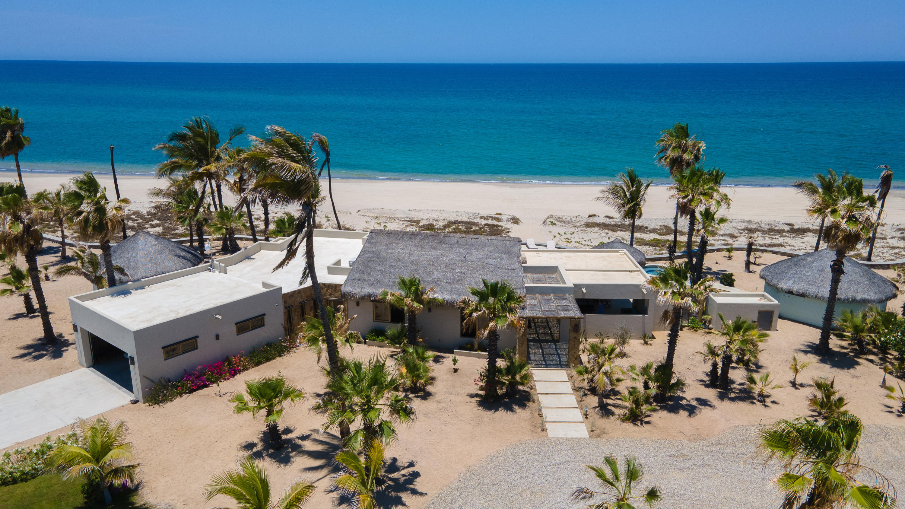 Beachfront Estate Property,  located in Playa Colorada with over two acres of land &100 meters of beach.   Casa de las Palmas is truly a ''one of a kind'' property which was remodeled in 2018 and featured in HGTV.  This estate has a main home with master en suite and the bunk room for your family or guests.Two more bedrooms and baths are located in the two casitas, located near the main house with views of the Sea.  And at the back of the property is a 1 bedroom casita with storage and full kitchen, which is currently occupied by the managers of the property.  This location  is great for families and corporate getaways and offers great attention to detail:  from the beach glass backsplash, pendant lites in the master suite, the swim-up bar in the pool, to the state of the art sound system heard throughout the home and pool area,  water filtration equipment, custom made doors and cabinets.    The great room area is the perfect place for entertaining,  and opens to the covered porch, pool, and hot tub area.  Watch the whales, gaze at the stars, or enjoy the breeze from the Sea.  Casa de la Palmas is a great place to unwind!   Want to hear or see more?  Contact us for a tour!  Coming soon: Virtual Tour of the property.