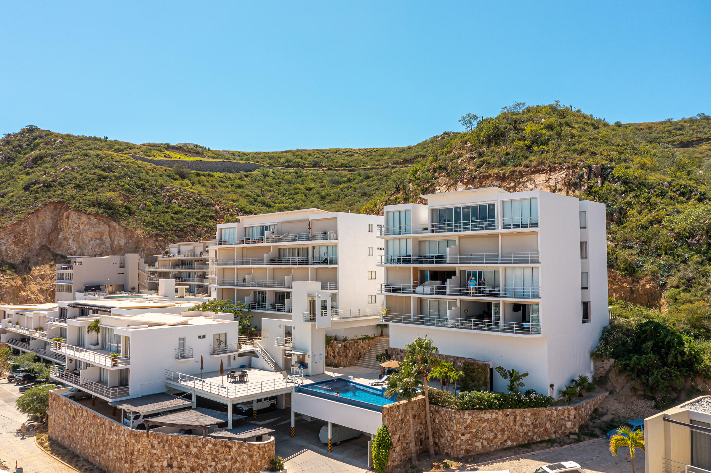 """Feel like you are living on top of the world in this newly remodeled two bedroom/bathroom condo featuring a stunning view of the Cabo marina and Sea of Cortez. The terrace is perfect for watching sunrise while sipping your morning coffee and catching an occasional whale swim by. The master bedroom has an impressive ocean view, ideal for waking up with the sun. Electric hurricane/sun blinds can easily be lowered for those lazy mornings. The second bedroom is currently being used as an office but can easily be converted back to a bedroom. The open floor plan with floor to ceiling windows create a bright and inviting living space perfectly coordinated for the easy living Cabo lifestyle. Cascadas offers 2 pool areas with BBQ's, Jacuzzi's, sun decks, and a Club House with full gym. Fully covered titled carport.  Full access to Pedregal amenities which included a secluded beach, spa, tennis courts, pickle ball, organic market, children's parks, and nearby hiking.  List of upgrades and additions:   New front door with peephole   New paint   New ceiling fans  Electronic Hurricane/sunscreens($13,000 value)   Water purification system  Smart doorbell, smart camera, smart smoke/carbon monoxide detector  New washing machine and dryer   Custom cabinets in laundry room   New light fixtures throughout the condo  All light switches and electrical outlet covers replaced  Living room and master bedroom windows resealed in May   New inverter mini-split AC, saving up to 70% of energy costs  73""""new TV and Sonos sound system in the living room   65""""new TV and Sonos sound system in the master bedroom   3 new Crate and Barrel rugs   Fiber optic (200 Mbps) Internet recently re-wired with brand new cabling and connection."""