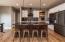 dark granite, white cabinets, dark island with storage.