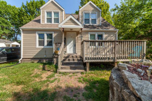 Large deck on front of house with covered entrance to unit A