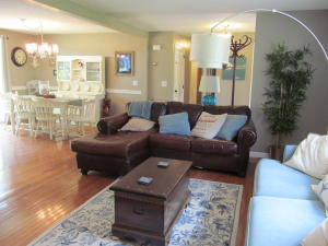 The living room open to the dining area and kitchen and features a gas fireplace, and wood floor .