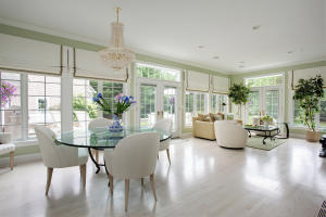 Gorgeous sun room leads to large deck with awning.